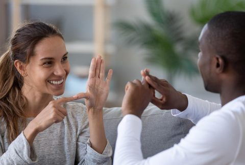 Smiling mixed ethnicity couple talking with sign language