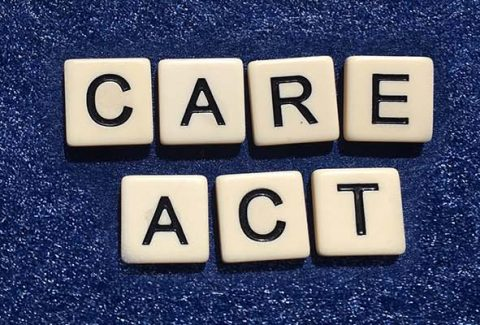 Scrabble tiles spelling out the words care act