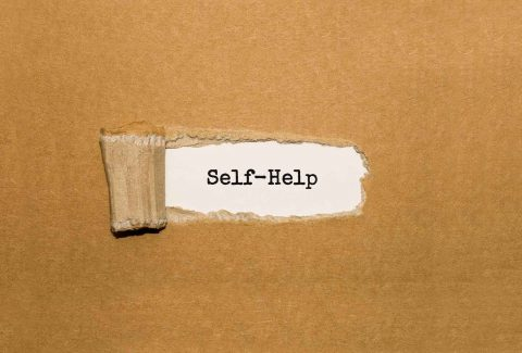 Torn paper revealing the words self help
