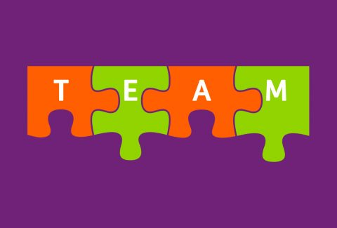 four jigsaw pieces linked together that make the word team
