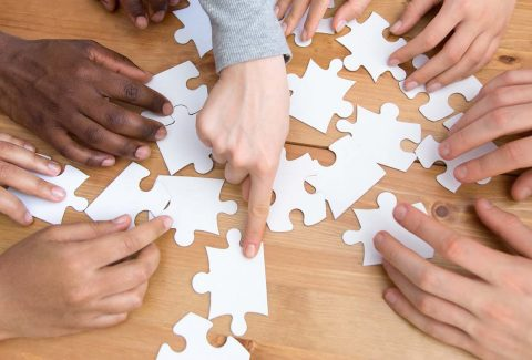 Close up hands of diverse people assembling puzzle